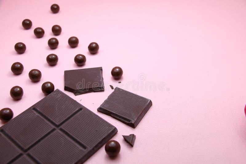 Pedazos de barra de chocolate oscura y de perlas del chocolate con leche en el fondo rosado, visión superior, espacio de la copia imagen de archivo