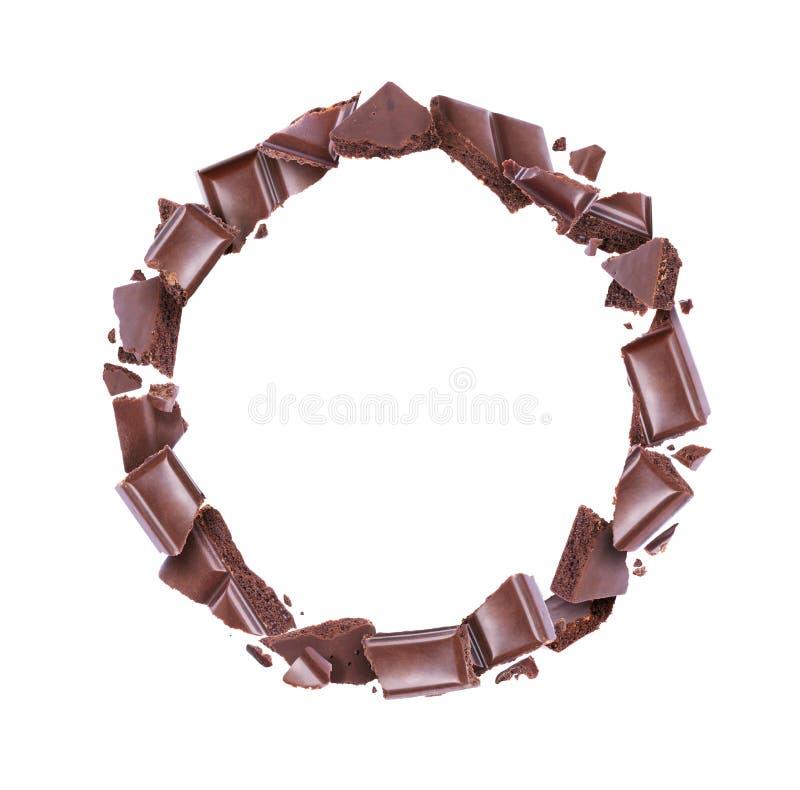 Pedazos de barra de chocolate porosa en un movimiento circular aislada en el fondo blanco fotografía de archivo