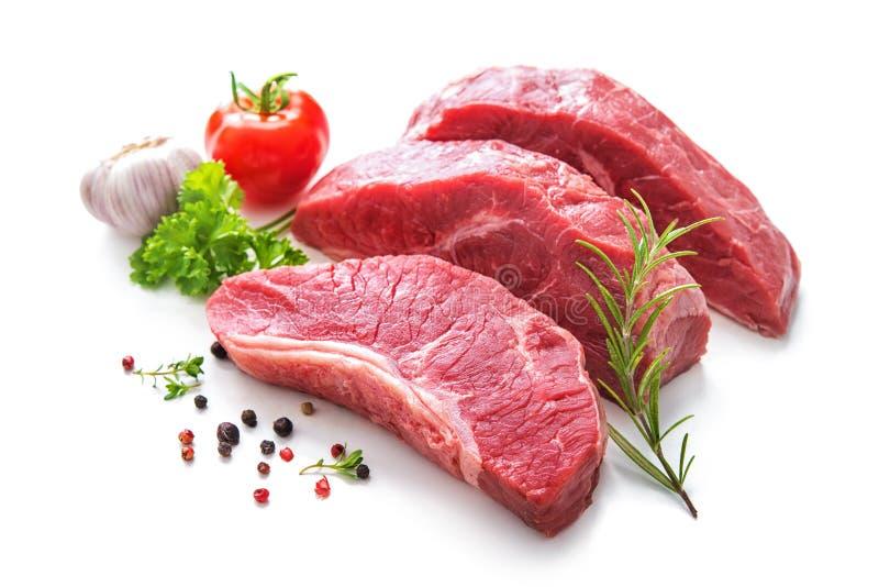 Pedazos de carne cruda del rosbif con los ingredientes imagen de archivo
