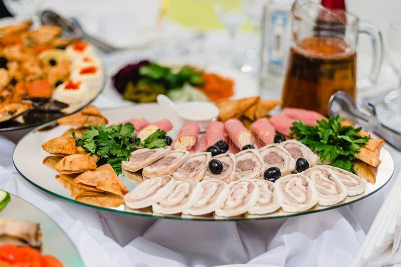 Pedazos de carne frescos apetitosos en la placa en el restaurante imagen de archivo