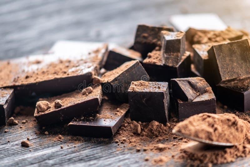 Pedazos de chocolate amargo oscuro con el polvo de cacao en fondo de madera oscuro Concepto de ingredientes de la confitería imagen de archivo libre de regalías