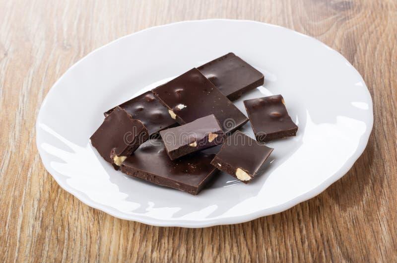 Pedazos de chocolate con la almendra en placa en la tabla fotos de archivo libres de regalías