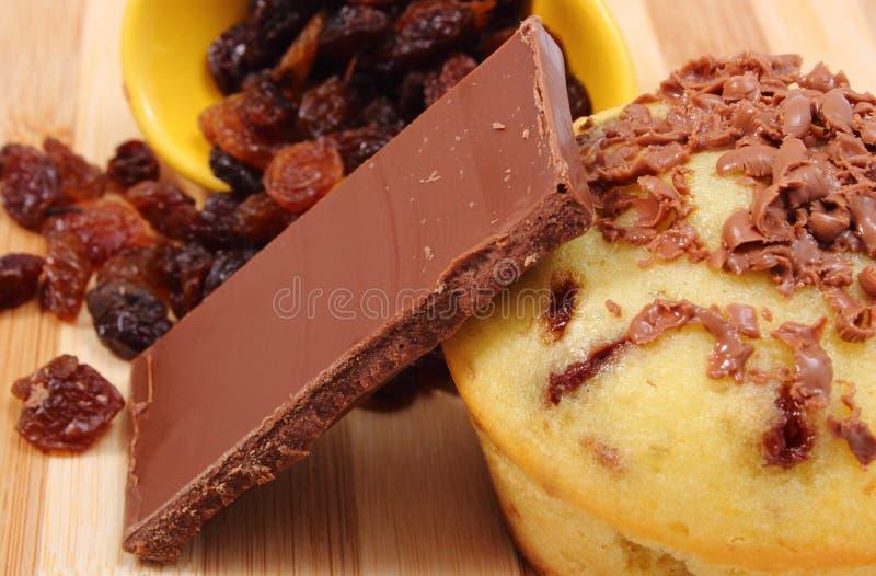 Pedazos de chocolate, de pasas y de mollete cocido fresco foto de archivo libre de regalías