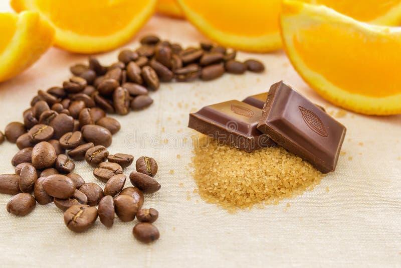 Pedazos de chocolate en el azúcar marrón, rodeados por las rebanadas anaranjadas foto de archivo libre de regalías