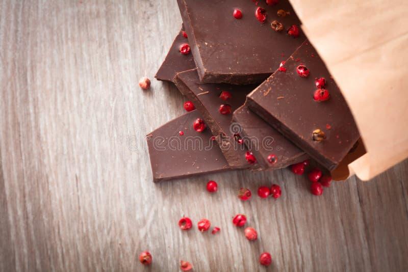 Pedazos de chocolate oscuro con pimienta rosada imagenes de archivo