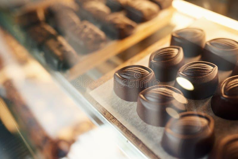 Pedazos de chocolate que se sientan en una vitrina de la tienda de la confitería imágenes de archivo libres de regalías