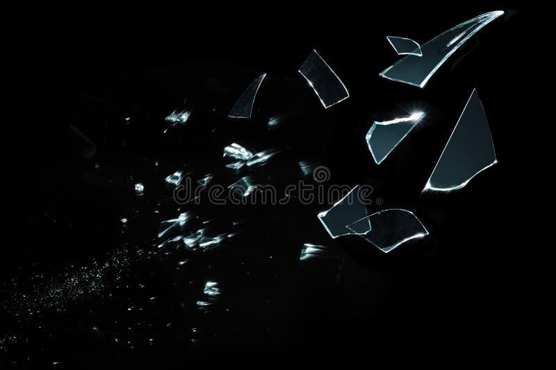 Pedazos de cristal rotos y splitted aislados en negro foto de archivo