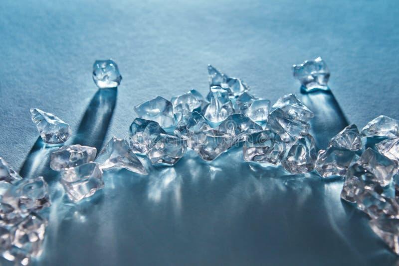Pedazos de cubos de hielo machacados en bajo la forma de arco con las sombras largas y de reflexiones en la superficie en un azul foto de archivo