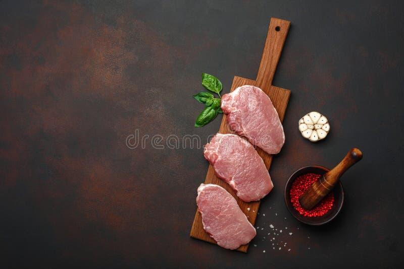 Pedazos de filete crudo del cerdo con albahaca, ajo, pimienta, el mortero de la sal y de la especia en tabla de cortar y el fondo fotos de archivo libres de regalías