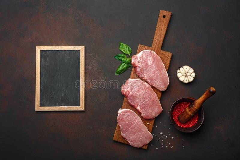 Pedazos de filete crudo del cerdo con albahaca, ajo, pimienta, el mortero de la sal y de la especia y el tablero de tiza en tabla imagen de archivo libre de regalías