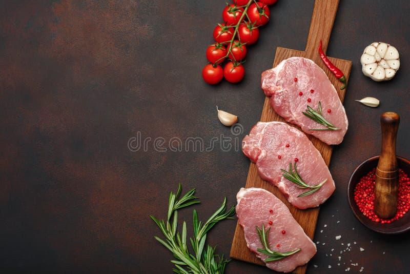 Pedazos de filete crudo del cerdo con albahaca, los tomates de cereza, el romero, el ajo, la pimienta, el mortero de la sal y de  foto de archivo