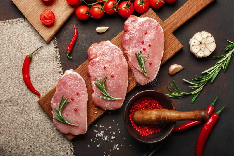 Pedazos de filete crudo del cerdo en tabla de cortar con el mortero de los tomates de cereza, del romero, del ajo, de la pimienta imagen de archivo libre de regalías