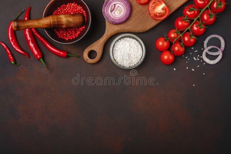 Pedazos de filete crudo del cerdo en tabla de cortar con los tomates de cereza, el romero, el ajo, la pimienta roja, la hoja de l foto de archivo libre de regalías