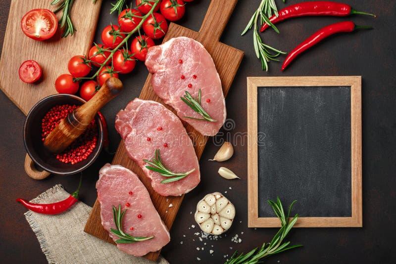 Pedazos de filete crudo del cerdo en tabla de cortar con los tomates de cereza, romero, ajo, pimienta, mortero de la sal y de la  imagen de archivo libre de regalías