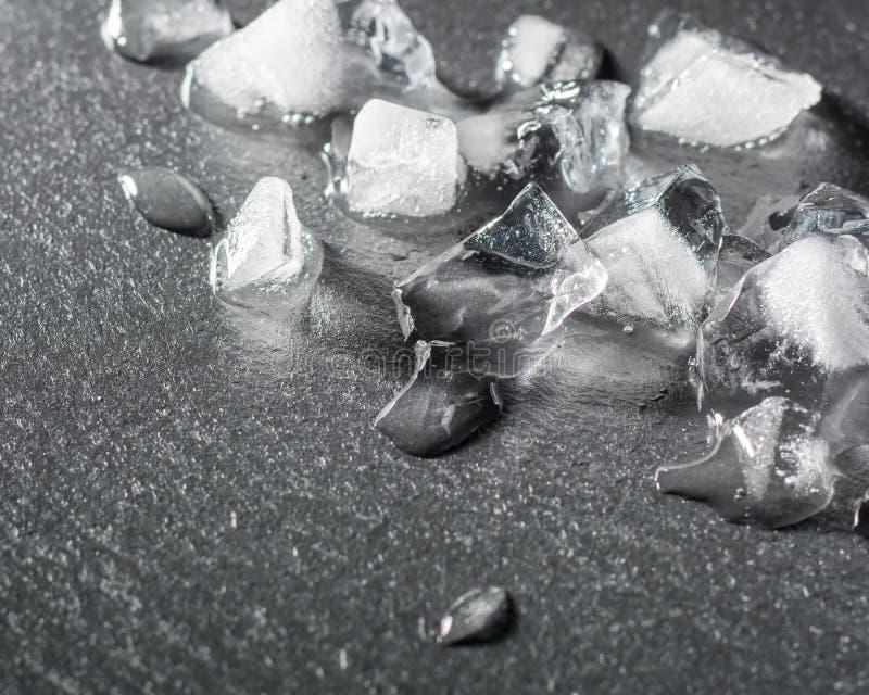 Pedazos de hielo machacado en una piedra negra Descensos del agua y del frío imagen de archivo libre de regalías