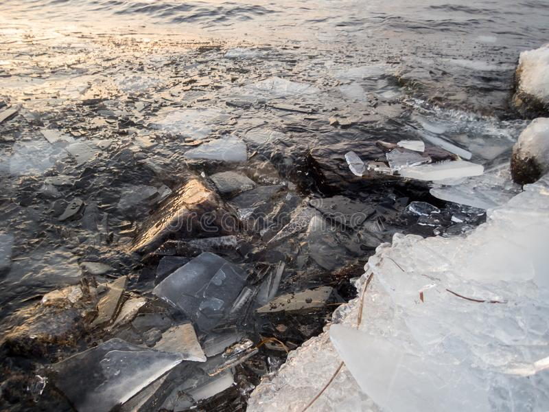 Pedazos de masas de hielo flotante de hielo en piedras de la orilla por un lago de congelación foto de archivo