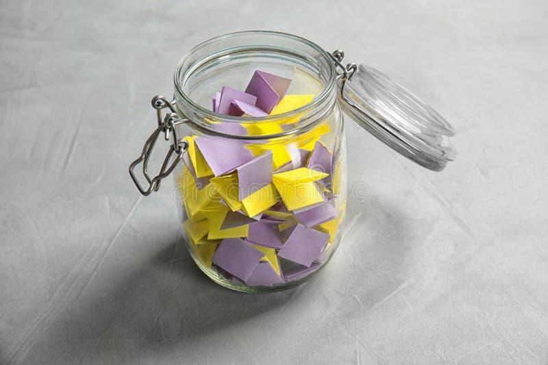 Pedazos de papel coloridos para la lotería en el tarro de cristal fotografía de archivo