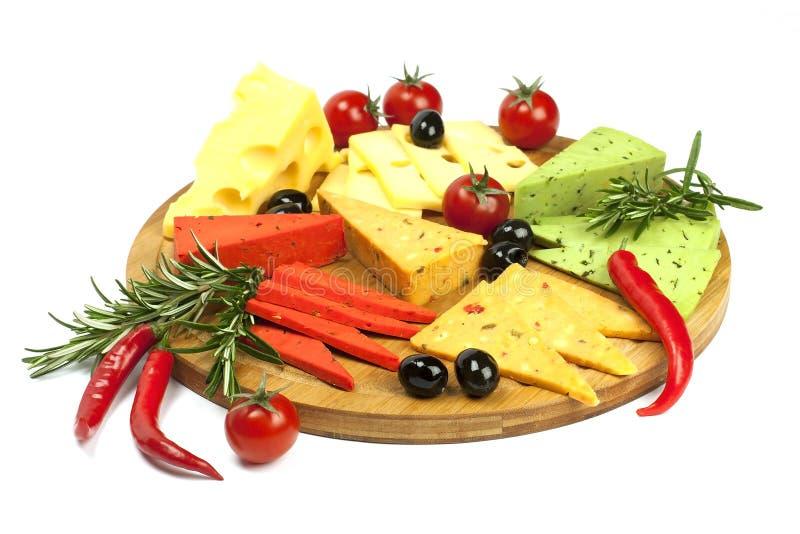 Pedazos de queso natural en un tablero de madera imagen de archivo