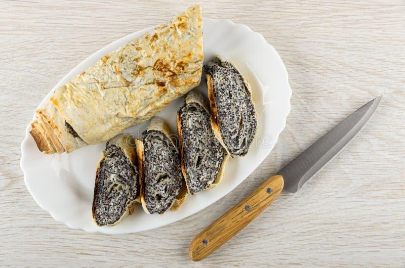 Pedazos de rollo cocido del pan Pita con el relleno del requesón, amapola en el plato, cuchillo en la tabla Visi?n superior imagen de archivo