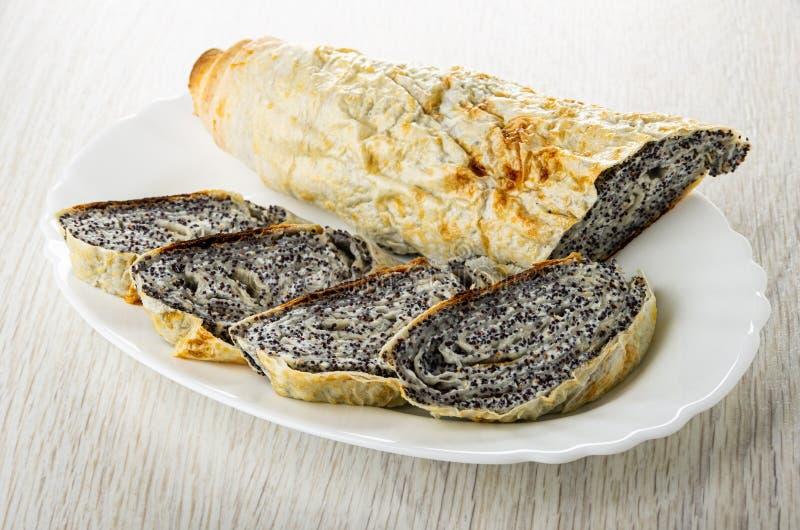 Pedazos de rollo cocido del pan Pita con el relleno del requesón, amapola en plato en la tabla foto de archivo libre de regalías