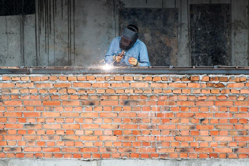 Pedazos de soldadura del hierro del trabajador de la industria en el nuevo edificio foto de archivo