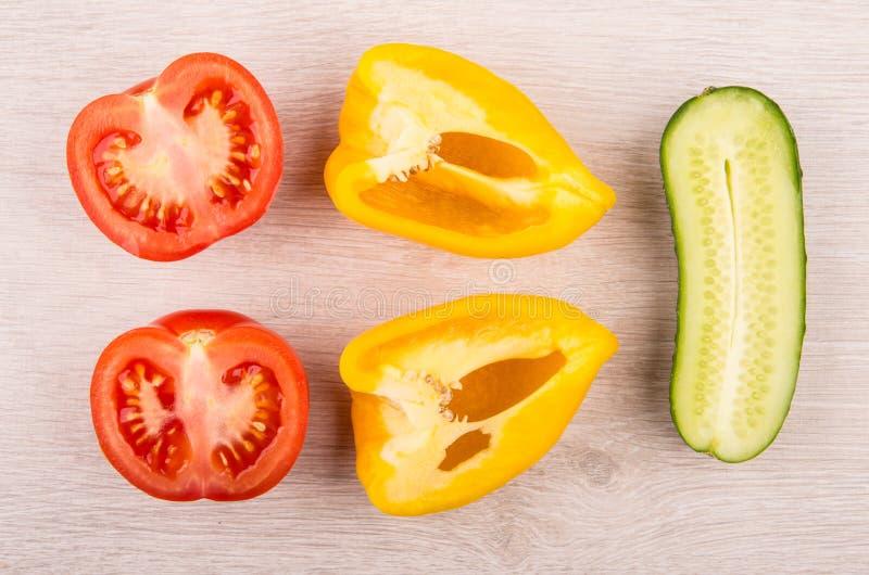 Pedazos de tomate, de pimienta dulce y de pepino en la tabla de madera fotos de archivo