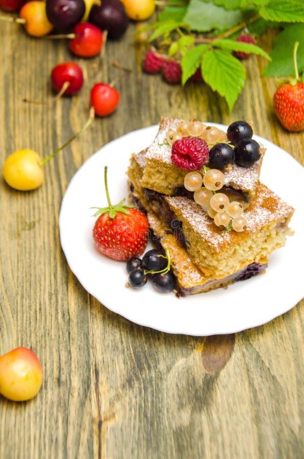 Pedazos de torta con las bayas y las bayas frescas de la pasa y de la cereza de la fresa en fondo de madera imagen de archivo libre de regalías