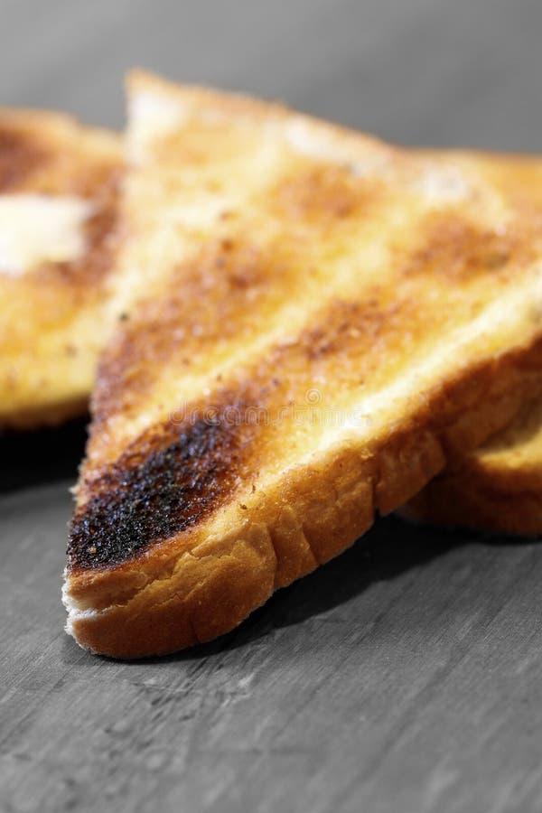 Pedazos de tostada del pan blanco con mantequilla en una superficie de madera imágenes de archivo libres de regalías