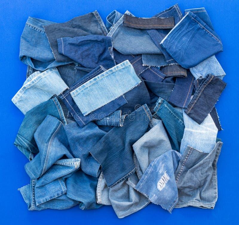 Pedazos de vaqueros del paño en un fondo azul fotografía de archivo libre de regalías