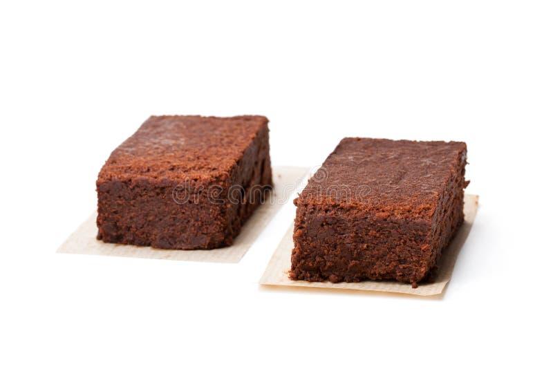 Pedazos del brownie del chocolate aislados en blanco fotografía de archivo