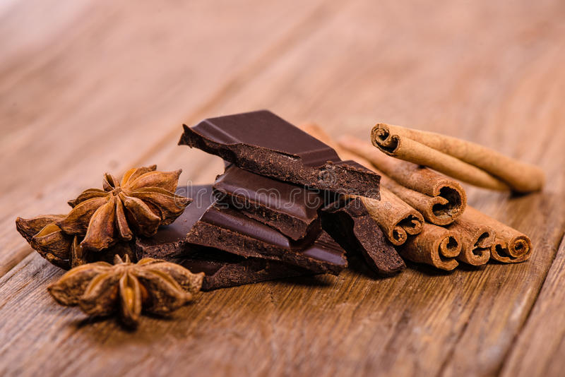 Pedazos del chocolate, anís de estrella y palillos de canela fotografía de archivo