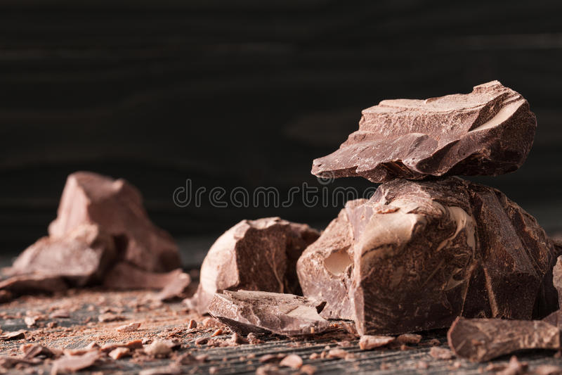 Pedazos del chocolate en un backround oscuro fotografía de archivo