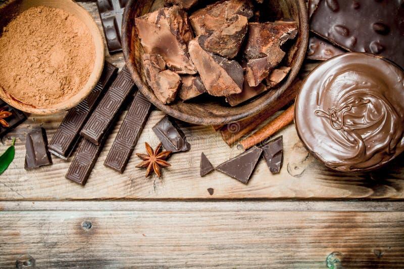 Pedazos del chocolate machacado con goma del chocolate y el cacao de tierra imagen de archivo