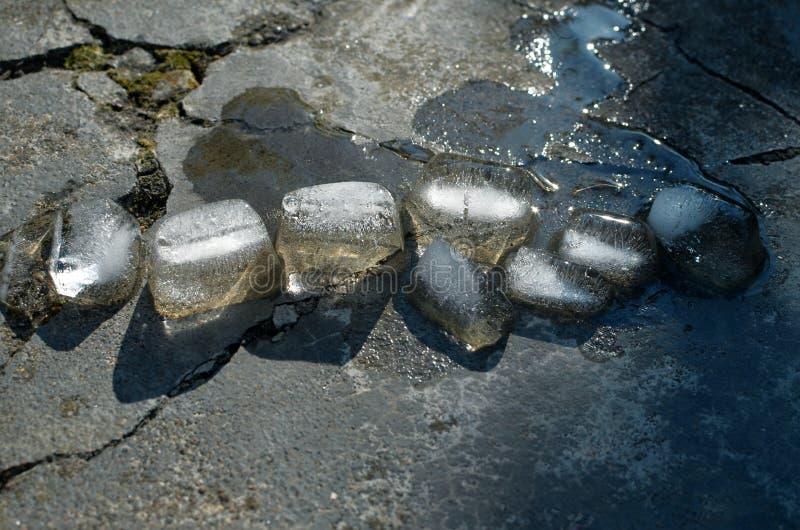 Pedazos del derretimiento del hielo en el pavimento agrietado y del resplandor en el sol foto de archivo