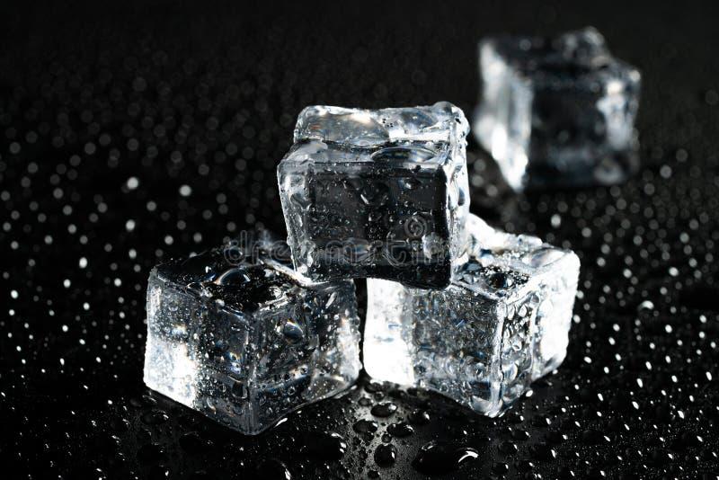 Pedazos del hielo y gotitas de agua fotos de archivo
