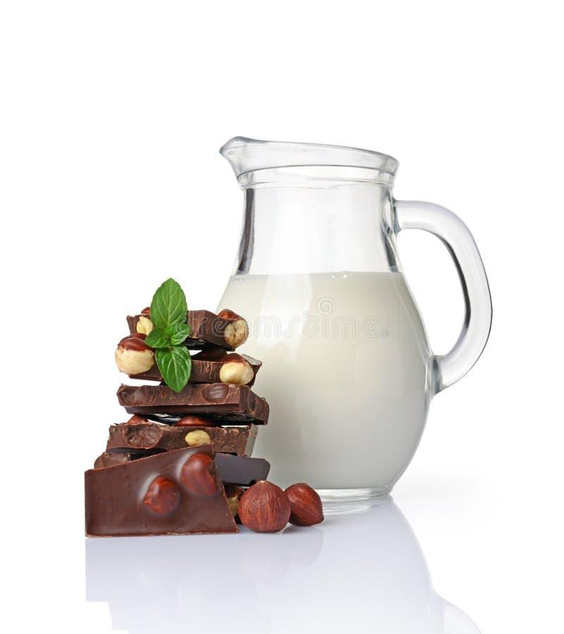 Pedazos del primer de barra de chocolate negra con las avellanas enteras y el jarro de cristal de leche foto de archivo