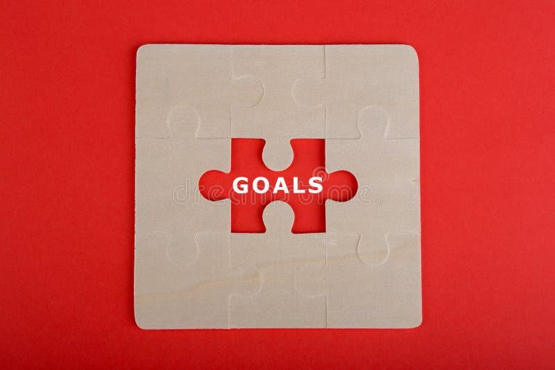 Pedazos del rompecabezas con palabras y x22; Goals& x22; en fondo rojo fotos de archivo libres de regalías