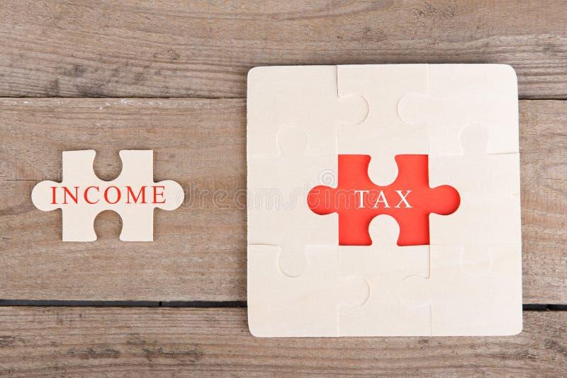 Pedazos del rompecabezas con palabras y x22; Tax& x22; y y x22; Income& x22; imagen de archivo libre de regalías