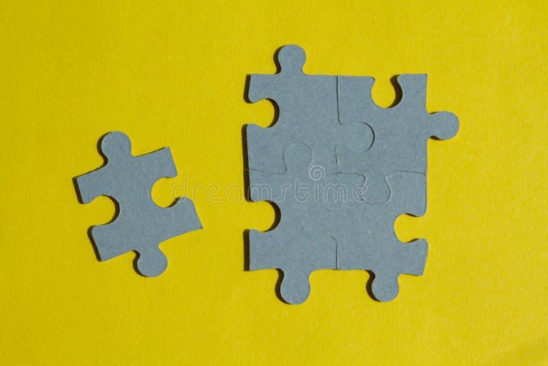 Pedazos del rompecabezas en fondo amarillo imágenes de archivo libres de regalías