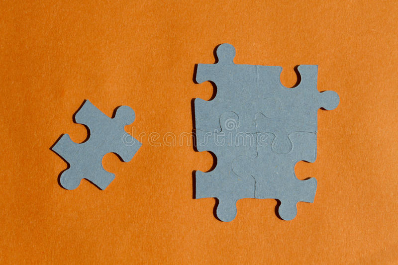 Pedazos del rompecabezas en fondo anaranjado fotografía de archivo libre de regalías