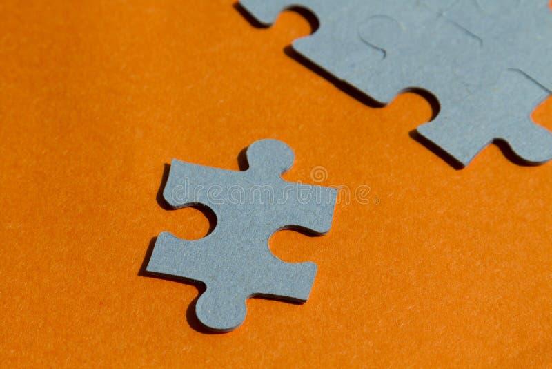 Pedazos del rompecabezas en fondo anaranjado brillante fotos de archivo libres de regalías