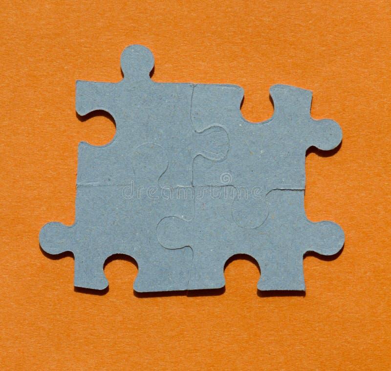Pedazos del rompecabezas en fondo anaranjado brillante foto de archivo