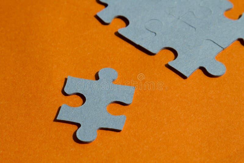 Pedazos del rompecabezas en fondo anaranjado brillante imágenes de archivo libres de regalías