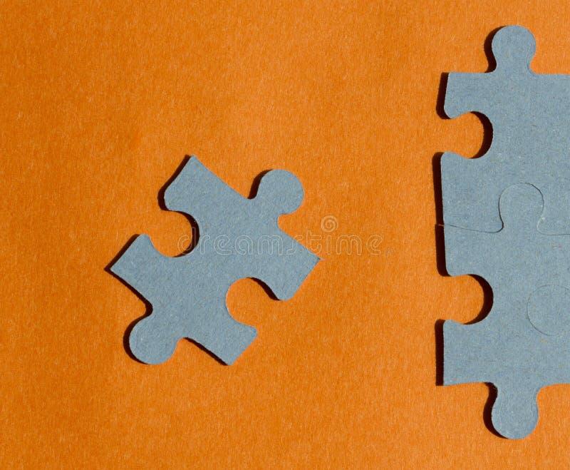 Pedazos del rompecabezas en fondo anaranjado brillante imagenes de archivo