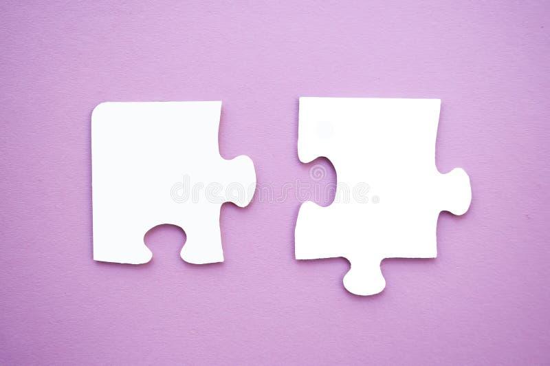 Pedazos del rompecabezas en fondo rosado Día de la conciencia del autismo imagen de archivo libre de regalías