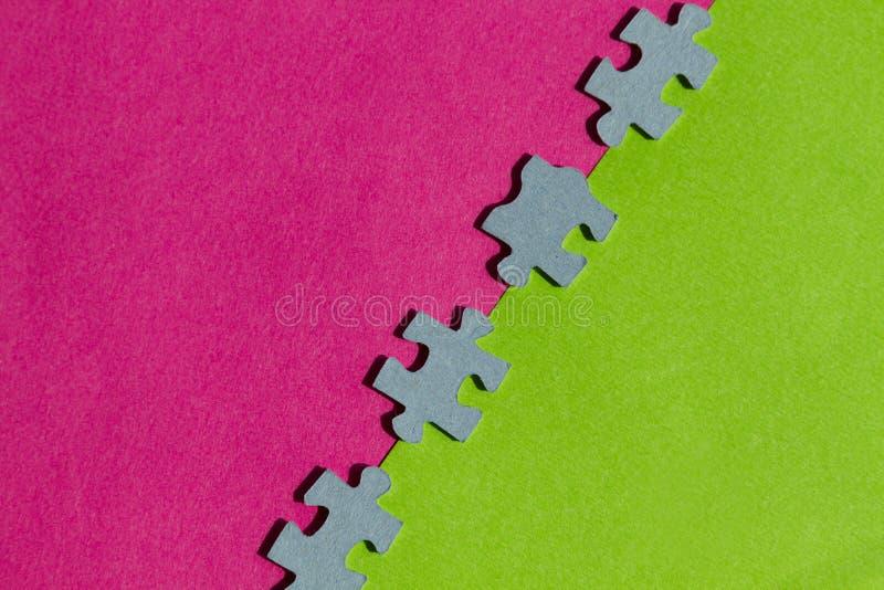 Pedazos del rompecabezas en fondo rosado y verde foto de archivo libre de regalías