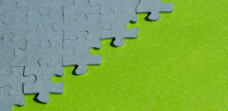 Pedazos del rompecabezas en fondo verde fotos de archivo libres de regalías