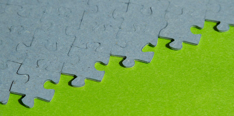 Pedazos del rompecabezas en fondo verde fotografía de archivo