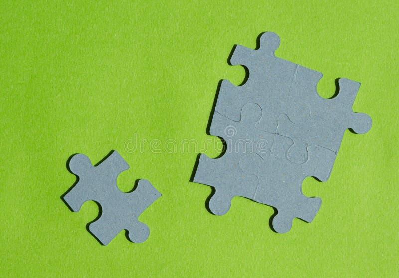 Pedazos del rompecabezas en fondo verde claro foto de archivo