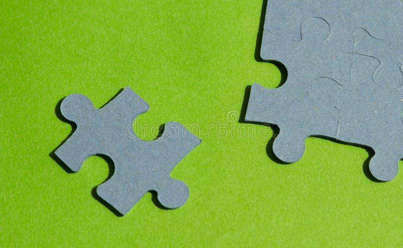 Pedazos del rompecabezas en fondo verde claro foto de archivo libre de regalías
